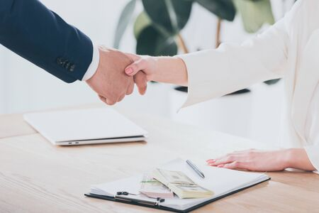 cropped shot of businessman shaking hands with client in office