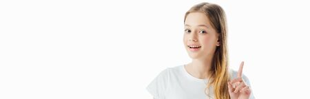 panoramic shot of happy teenage girl showing idea gesture and looking at camera isolated on white