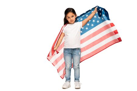 cute latin kid in denim jeans standing with american flag isolated on white
