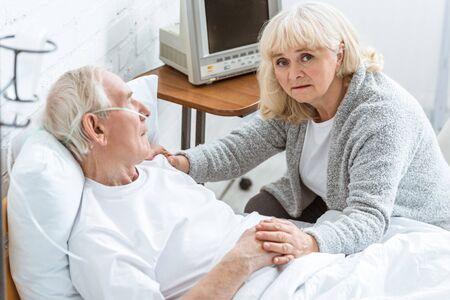 sad senior woman with sick husband in hospital Stock Photo