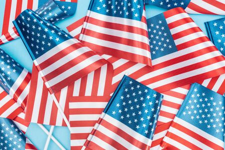 top view of national american flags on sticks scattered on blue background Stock Photo