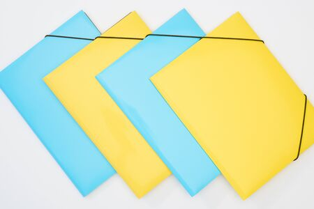 flat lay of yellow and blue folders on white background