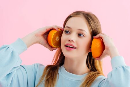 smiling pretty teenage girl holding orange halves near ears isolated on pink Stock Photo - 125331930