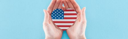partial view of woman holding heart made of  national american flag on blue background, panoramic shot
