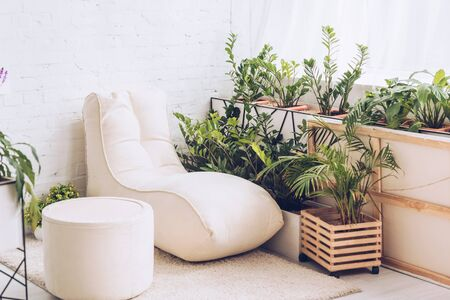 white soft chaise lounge and pouf in room with lush green plants