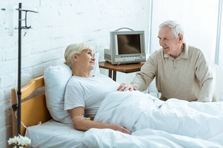 smiling sick senior woman looking at husband in clinic