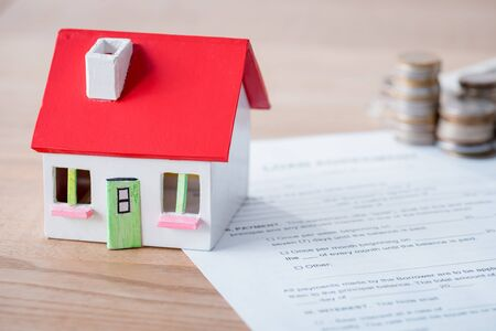 house model, loan agreement and stacks of metal coins on wooden surface Stock Photo