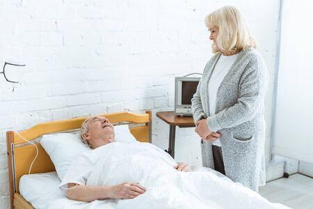 senior woman standing near sick husband in hospital