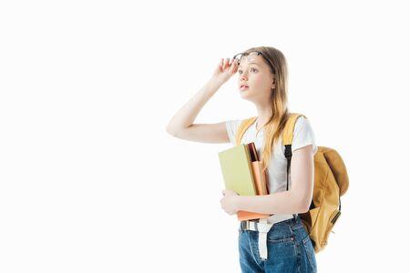 Nieuwsgierig schoolmeisje met rugzak die boeken vasthoudt en wegkijkt geïsoleerd op wit