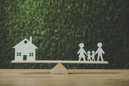 paper cut house and paper family balancing on seesaw on green background Reklamní fotografie