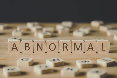 selective focus of abnormal lettering on cubes surrounded by blocks with letters on wooden surface isolated on black