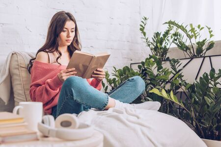 selective focus of focused young woman reading book while sitting with crossed legs near green plants at home