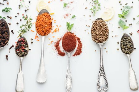 top view of spices in silver spoons near herbs and lemon slices on white background