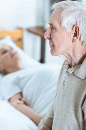 sad senior man and senior woman in coma in hospital