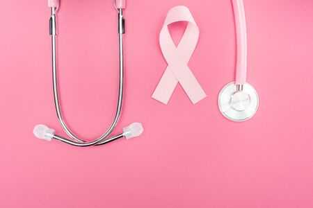 flat lay with stethoscope and pink breast cancer sign on pink background with copy space Zdjęcie Seryjne
