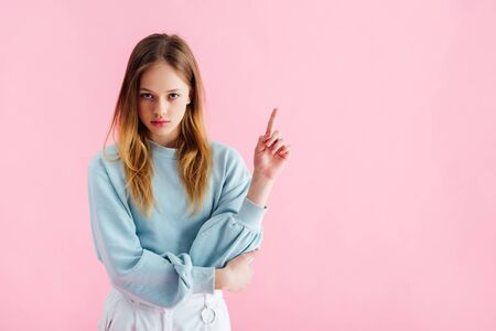 sad teenage girl pointing with finger isolated on pink