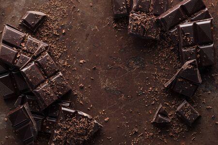 Vista dall'alto di pezzi di barretta di cioccolato con scaglie di cioccolato su sfondo di metallo ruggine