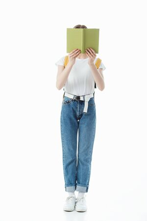 schoolgirl with backpack holding book in front of face isolated on white