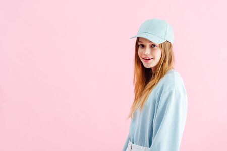 happy pretty teenage girl in cap looking at camera isolated on pink