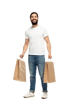 happy latin man holding shopping bags and smiling isolated on white Banco de Imagens
