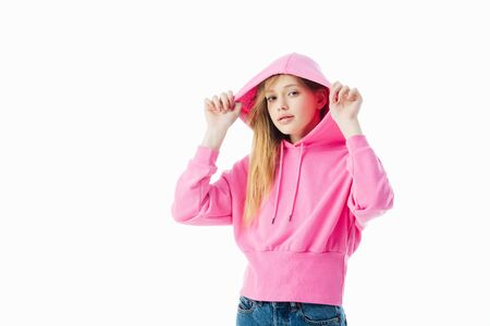 stylish teenage girl in pink hoodie looking at camera isolated on white