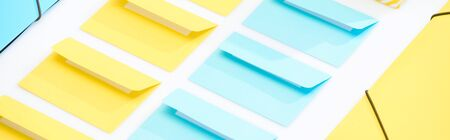 panoramic shot of yellow and blue folders and opened envelopes on white background Stock Photo