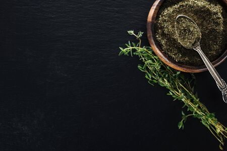 top view of dried thyme in wooden bowl with spoon near green herb on black background