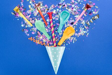 Top view of party colorful decoration on blue background, surprise concept