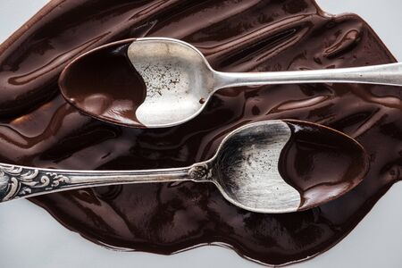 Top view of spoons covered of chocolate and melted chocolate on white background