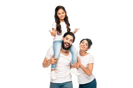 Feliz padre latino llevando sobre hombros linda hija mostrando los pulgares para arriba cerca de la esposa feliz aislado en blanco