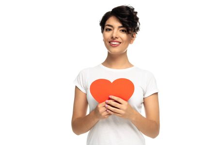 cheerful latin woman holding red heart-shape carton isolated on white Stock fotó