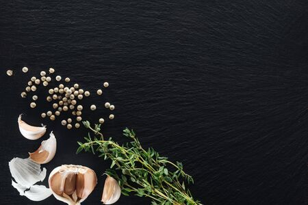 top view of white pepper on black background near garlic cloves and thyme Фото со стока