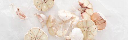 panoramic shot of cut garlic cloves on white paper background Banco de Imagens