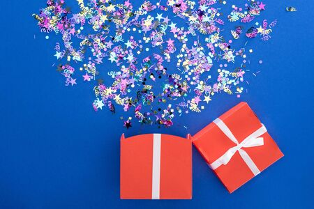 red gift box and multicolored shiny confetti on blue background
