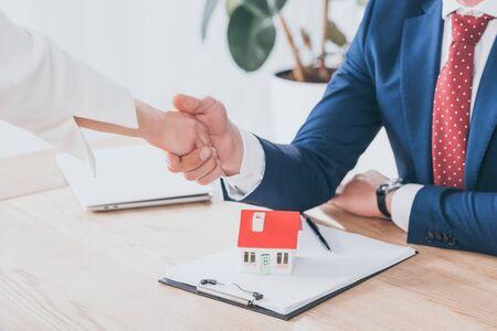 Teilansicht von Geschäftsmann und Kunde beim Händeschütteln in der Nähe des Hausmodells auf dem Tisch Standard-Bild