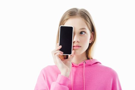 teenage girl in pink hoodie holding smartphone with blank screen in front of face isolated on white