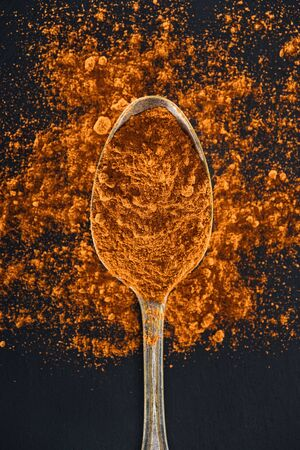 top view of turmeric in silver spoon on black background