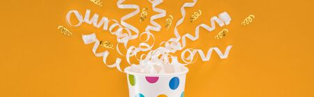Panoramic shot of white ribbons and polka dot paper cup on orange background