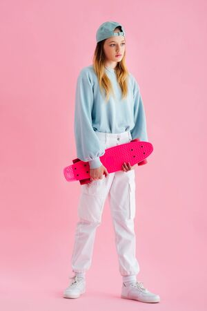 pretty teenage girl in cap holding penny board on pink
