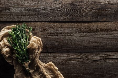 top view of green rosemary in rustic cloth on wooden weathered table with copy space