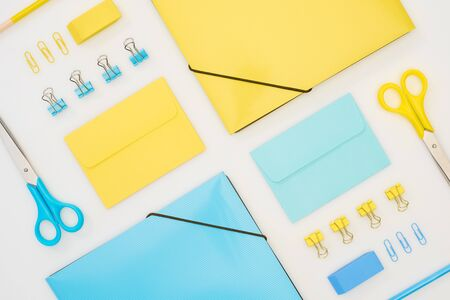 flat lay of blue and yellow folders, envelopes, scissors, pencils, erasers and paper clips isolated on white Stock Photo