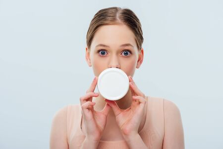 teenage girl with obscure face holding cosmetic cream isolated on grey