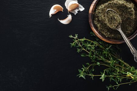 top view of dried thyme in wooden bowl with silver spoon near green herb and garlic cloves on black background