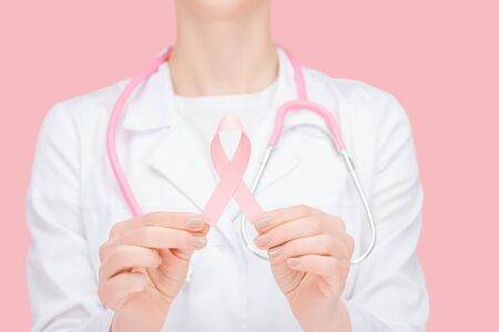 selective focus of doctor in white coat holding pink cancer sign isolated on pink Stock Photo