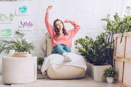 smiling girl stretching while sitting on soft chaise lounge near pouf and lush green plants 写真素材