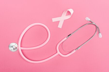 top view of stethoscope and pink cancer sign on pink background