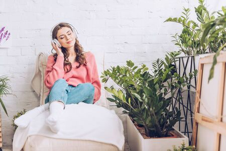 pretty girl with closed eyes relaxing while sitting in soft chaise lounge and listening music in headphones