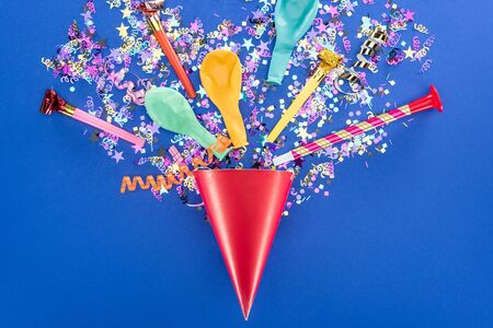 Top view of festive red party hat on blue background
