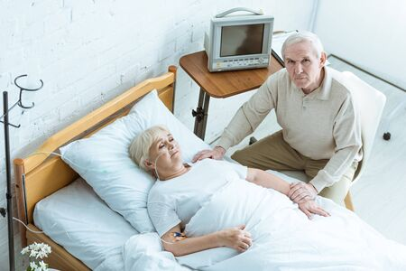 overhead view of sick senior woman with husband in clinic