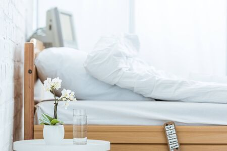 empty bed, orchids and glass of water in hospital ward Фото со стока